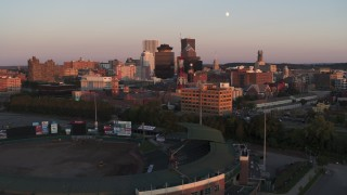 DX0002_209_044 - 5.7K stock footage aerial video reverse view of First Federal Plaza and radio tower at sunset, reveal stadium, Downtown Rochester, New York