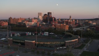 DX0002_209_045 - 5.7K stock footage aerial video ascend by baseball stadium to approach radio tower at sunset, Downtown Rochester, New York