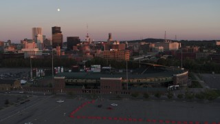 DX0002_209_046 - 5.7K stock footage aerial video fly away from office buildings and radio tower at sunset, reveal stadium, Downtown Rochester, New York