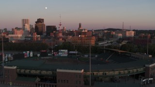 DX0002_209_048 - 5.7K stock footage aerial video fly over baseball stadium to approach radio tower and office buildings at sunset, Downtown Rochester, New York