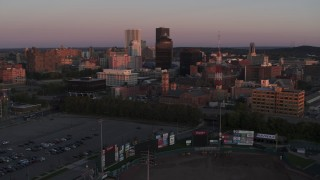 DX0002_209_051 - 5.7K stock footage aerial video reverse view of a radio tower and office buildings at sunset, Downtown Rochester, New York