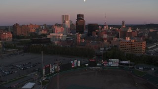 DX0002_209_052 - 5.7K stock footage aerial video of flying by a radio tower and office buildings at sunset, Downtown Rochester, New York