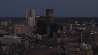 DX0002_210_008 - 5.7K stock footage aerial video descend and focus on Legacy Tower at twilight while passing radio tower, Downtown Rochester, New York