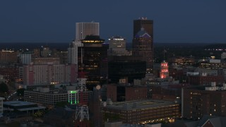 DX0002_210_018 - 5.7K stock footage aerial video descend and orbit the city skyline behind radio tower, First Federal Plaza at twilight, Downtown Rochester, New York