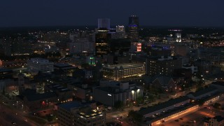 DX0002_210_023 - 5.7K stock footage aerial video descend and fly away from the city's skyline at night, Downtown Rochester, New York
