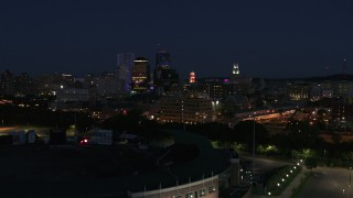 DX0002_210_026 - 5.7K stock footage aerial video reverse view of office buildings, reveal stadium at night, Downtown Rochester, New York