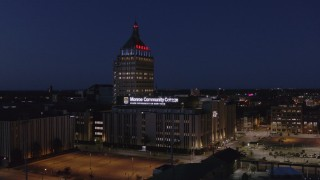 DX0002_210_035 - 5.7K stock footage aerial video ascend toward Kodak Tower and college at night, Rochester, New York