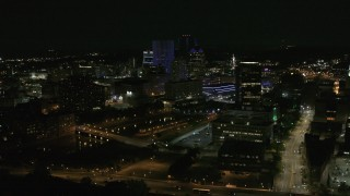 DX0002_210_045 - 5.7K stock footage aerial video fly away from and orbit city's skyline beside the Genesee River at night, Downtown Rochester, New York