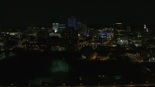 DX0002_210_049 - 5.7K stock footage aerial video of a view of the city's skyline, the Genesee River, and High Falls at night, Downtown Rochester, New York