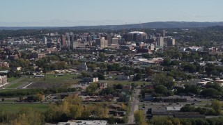DX0002_211_020 - 5.7K stock footage aerial video of passing by Downtown Syracuse, New York seen from across the city