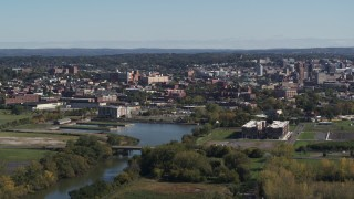 DX0002_211_037 - 5.7K stock footage aerial video of an apartment complex beside Onondaga Creek, Downtown Syracuse in background, New York