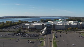 DX0002_212_021 - 5.7K stock footage aerial video of flying away from the Destiny USA shopping mall with lake in the background, Syracuse, New York