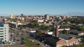DX0002_212_033 - 5.7K stock footage aerial video fly over building with smoke stack toward the city's downtown area, Downtown Syracuse, New York
