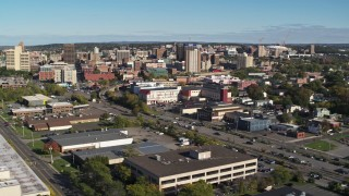 DX0002_212_034 - 5.7K stock footage aerial video descend near office buildings with view of the city's downtown area, Downtown Syracuse, New York