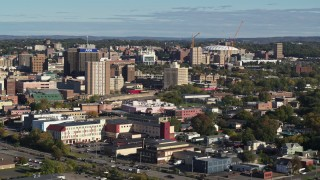 DX0002_213_012 - 5.7K stock footage aerial video of Carrier Dome stadium behind office buildings in Downtown Syracuse, New York