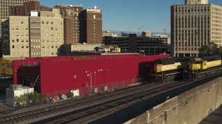 DX0002_214_003 - 5.7K stock footage aerial video descend and track a train in Downtown Syracuse, New York