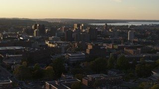 DX0002_214_022 - 5.7K stock footage aerial video focus on downtown, seen from campus buildings at Syracuse University at sunset, New York
