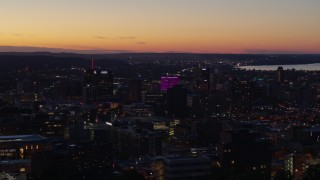 DX0002_214_037 - 5.7K stock footage aerial video of flying by office and city buildings lit up for the evening in Downtown Syracuse at sunset, New York
