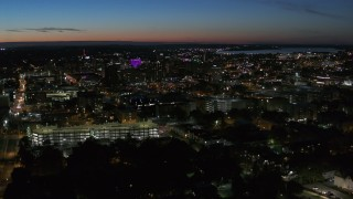 DX0002_215_002 - 5.7K stock footage aerial video of flying by city buildings lit up for the evening in Downtown Syracuse at twilight, New York