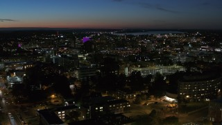 DX0002_215_003 - 5.7K stock footage aerial video of a wide view of city buildings lit up for the evening in Downtown Syracuse at twilight, New York