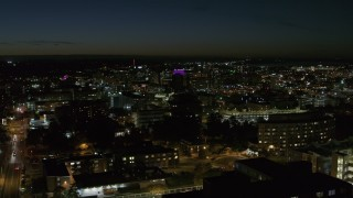 DX0002_215_021 - 5.7K stock footage aerial video descend by Syracuse University at twilight while focused on Downtown Syracuse, New York