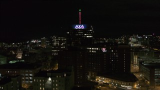 DX0002_215_032 - 5.7K stock footage aerial video of orbiting an office tower and hotel at night, Downtown Syracuse, New York
