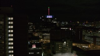 DX0002_215_034 - 5.7K stock footage aerial video flyby apartment complex to reveal office tower and hotel at night, Downtown Syracuse, New York