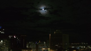 DX0002_215_042 - 5.7K stock footage aerial video of the moon above the 500 Building at night, reveal apartment building, Downtown Syracuse, New York