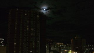 DX0002_215_043 - 5.7K stock footage aerial video of the moon while flying by apartment building, Downtown Syracuse, New York
