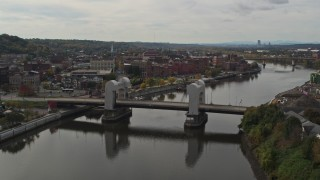 DX0002_216_011 - 5.7K stock footage aerial video descend and fly away from the downtown area of Troy, New York, reveal a bridge