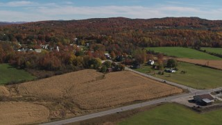 DX0002_217_010 - 5.7K stock footage aerial video of flying away from a small town beside a forest in autumn, Orwell, Vermont