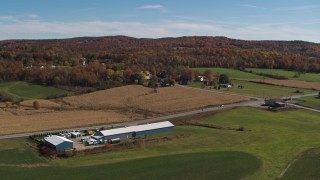 DX0002_217_011 - 5.7K stock footage aerial video descend and flyby a country road beside a small town in autumn, Orwell, Vermont