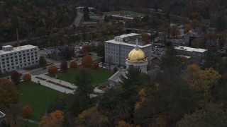 DX0002_219_018 - 5.7K stock footage aerial video reverse view of the capitol while flying above trees, Montpelier, Vermont