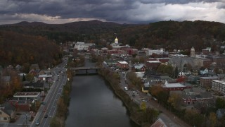 DX0002_220_017 - 5.7K stock footage aerial video of flying by a bridge on the river with a view of the state capitol at sunset, Montpelier, Vermont