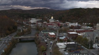 DX0002_220_018 - 5.7K stock footage aerial video of flying over a bridge on the river with a view of the state capitol at sunset, Montpelier, Vermont