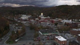DX0002_220_019 - 5.7K stock footage aerial video of a stationary and reverse view of the state capitol at sunset from the river, Montpelier, Vermont