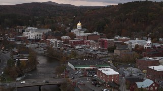 DX0002_220_025 - 5.7K stock footage aerial video ascend and fly away from capitol dome at sunset seen from the river, Montpelier, Vermont