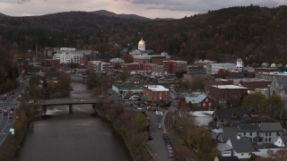 DX0002_220_026 - 5.7K stock footage aerial video descend by the river with a view of the capitol dome at sunset, Montpelier, Vermont