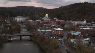 DX0002_220_027 - 5.7K stock footage aerial video ascend over a bridge while focused on the capitol dome at sunset, Montpelier, Vermont