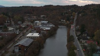 DX0002_220_037 - 5.7K stock footage aerial video of flying over the river and Berlin Street to approach grocery store at sunset, Montpelier, Vermont