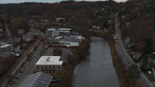 DX0002_220_038 - 5.7K stock footage aerial video of flying away from a grocery store by the river at sunset, Montpelier, Vermont