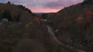 DX0002_220_042 - 5.7K stock footage aerial video of a road between hills with colorful trees at sunset, Montpelier, Vermont