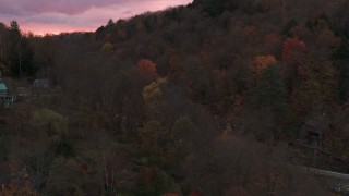 DX0002_220_043 - 5.7K stock footage aerial video of orbiting and flying away from hills with colorful trees at sunset, Montpelier, Vermont