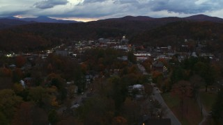 DX0002_220_053 - 5.7K stock footage aerial video of a view of the downtown area of the city seen from homes and fall trees at twilight, Montpelier, Vermont