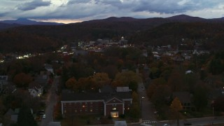 DX0002_220_054 - 5.7K stock footage aerial video of flying by the downtown area of the city seen from homes and fall trees at twilight, Montpelier, Vermont