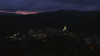 DX0002_220_062 - 5.7K stock footage aerial video of flying by downtown buildings around the capitol dome lit up at twilight, Montpelier, Vermont