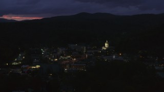 DX0002_220_063 - 5.7K stock footage aerial video of passing by city buildings around the capitol dome lit up at twilight, Montpelier, Vermont