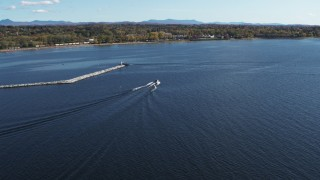 DX0002_224_026 - 5.7K stock footage aerial video of tracking a speedboat racing past a breakwater on Lake Champlain near Burlington, Vermont