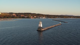 DX0002_225_008 - 5.7K stock footage aerial video fly low over Lake Champlain lighthouse toward downtown at sunset, Burlington, Vermont