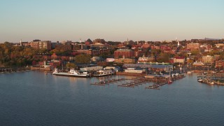 DX0002_225_012 - 5.7K stock footage aerial video fly away from and orbit buildings in downtown behind marinas at sunset, Burlington, Vermont